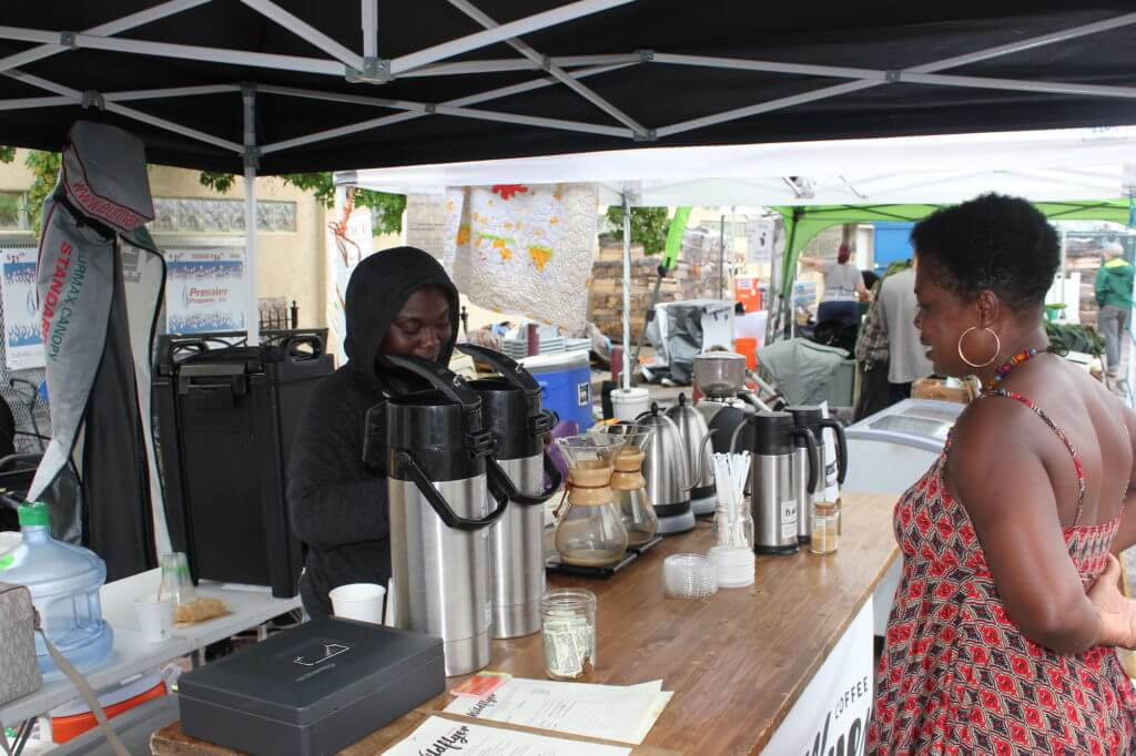 Koliesha Banks serves a customer at the Wildflyer Coffee stand at the Linden Hills Farmers Market. Wildflyer is raising funds to find a permanent location so they can employ more unstably housed youth and provide them with regular hours. Photo by Andrew Hazzard